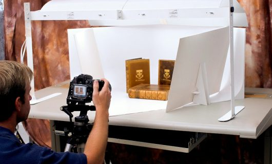 man taking picture of books in product photography lightbox
