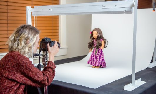 woman taking photo of doll in photo lightbox